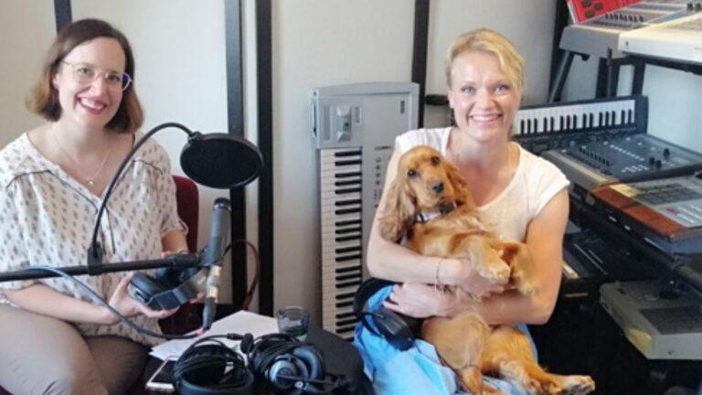 Kati Palsanen ja Maaret Kallio sylissään koira istuvat studiossa