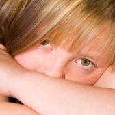 Surullinen tyttö katsoo kameraan käsivarsiensa takaa