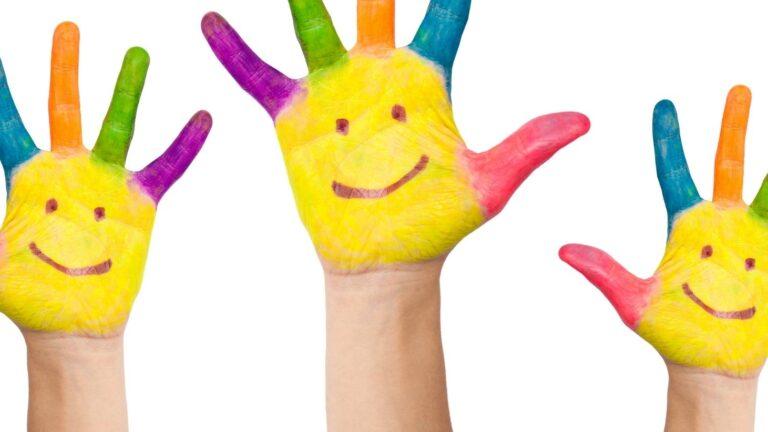 Maalatut kädet ilmassa.
