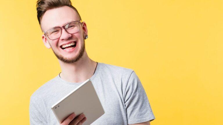 Nuori mies pitää kädessään tablettititokonetta hymyillen.