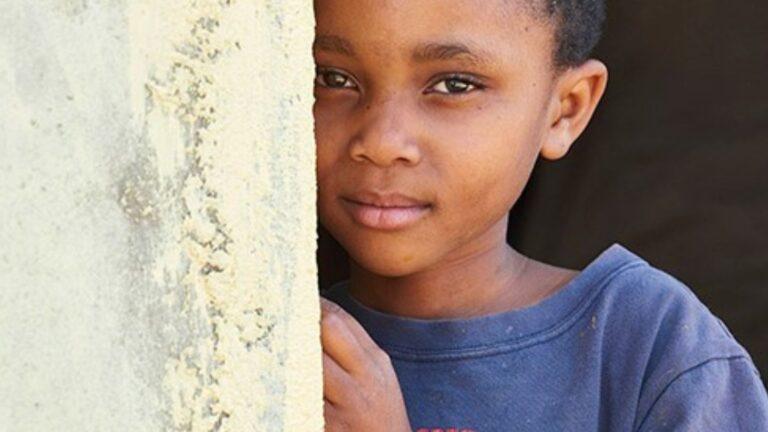 Pieni poika kurkkii seinän takaa