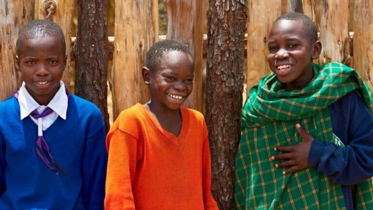 Kolme tansanialaispoikaa nauraa