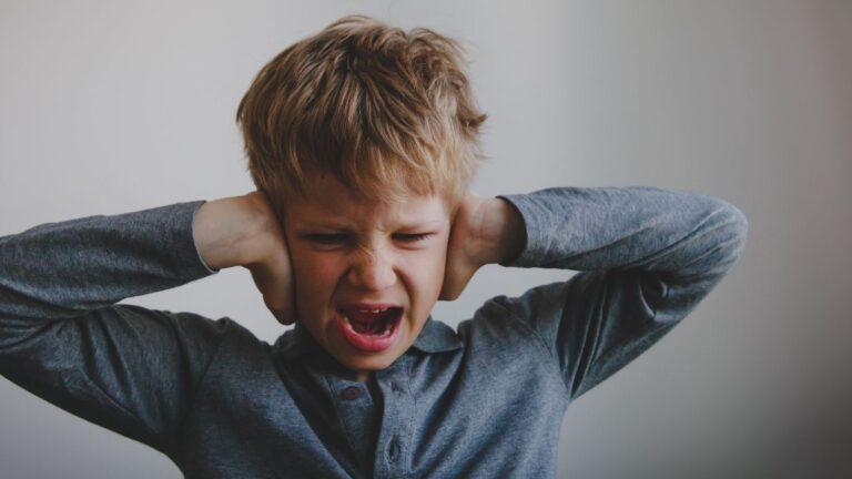 Vihainen lapsi kädet korvillaan