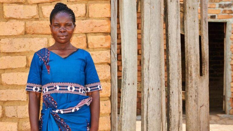 Tansanialainen nainen seisoo tiiliseinän edessä