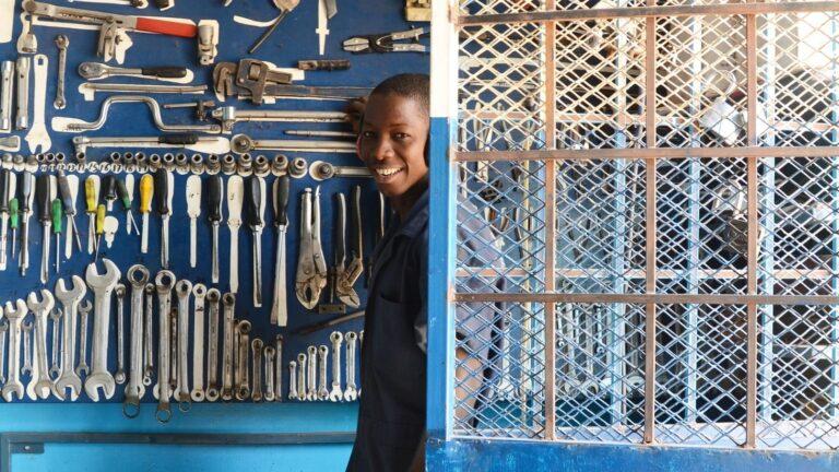 Gambialainen nuori työskentelemässä autokorjaamolla työkaluseinän edessä