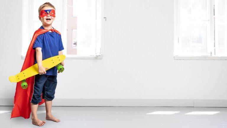 Supersankariasuun pukeutunut poika skeittilauta kainalossa.
