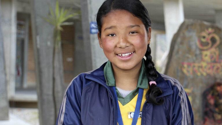 Nepalilainen koulutyttö hymyilee