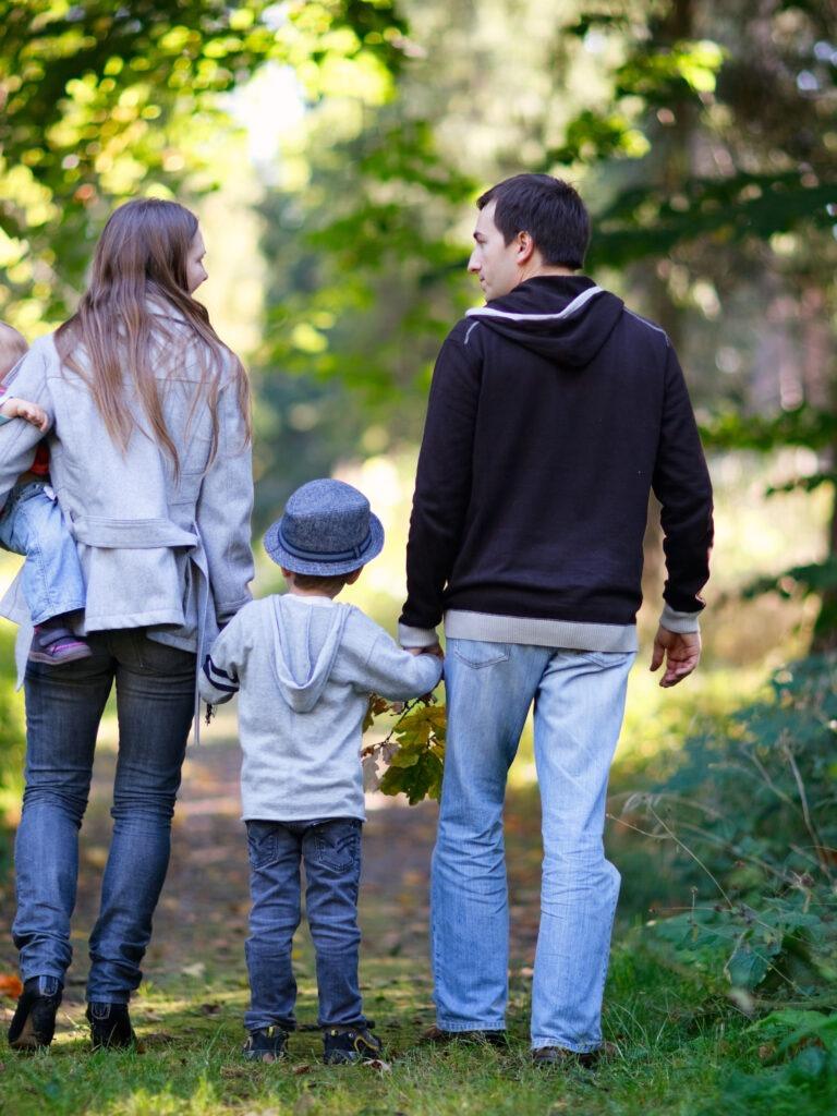 nuori perhe kävelyllä metsässä