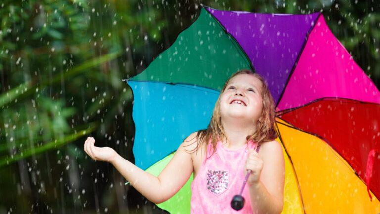 Tyttö värikkään sateenvarjon kanssa sateessa