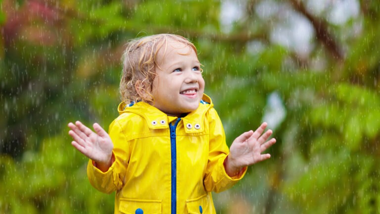 lapsi leikkii sateessa sadetakki päällä