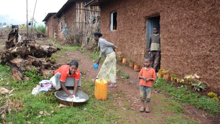 Etiopialaisäiti kotinsa edustalla tekemässä arkiaskareita