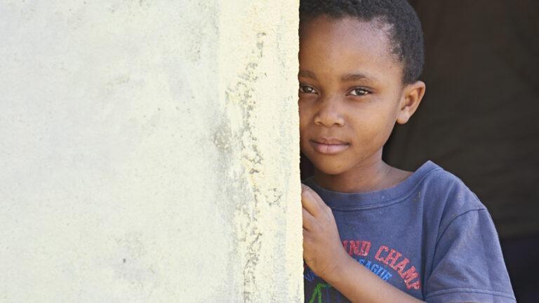 Afrikkalainen poika kurkistaa seinän takaa.
