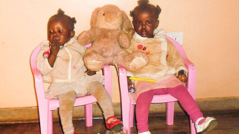 Sambialaiskaksostytöt istuvat vaaleanpunaisilla tuoleilla pehmopupu välissään.