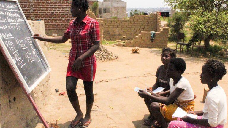 Mosambikilaistyttö opettaa pienempiä lapsia liitutaulun avulla