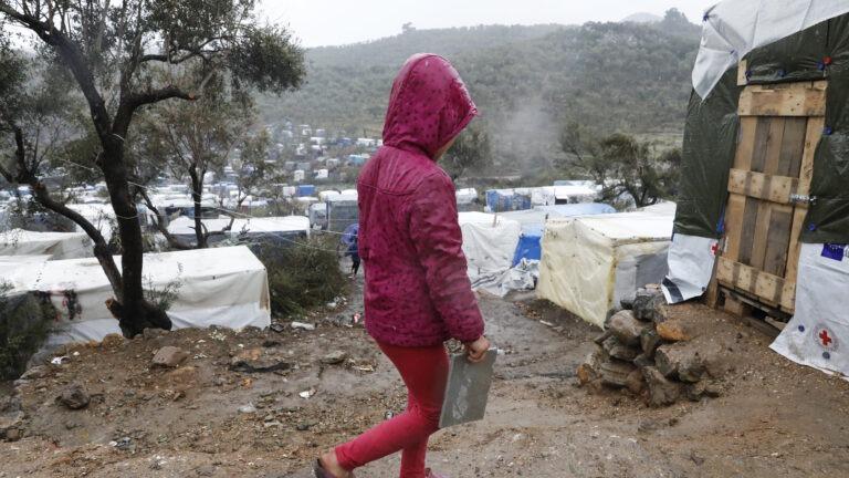 Tyttö punaisessa takissaan kävelee pakolaisleirillä Kreikassa.