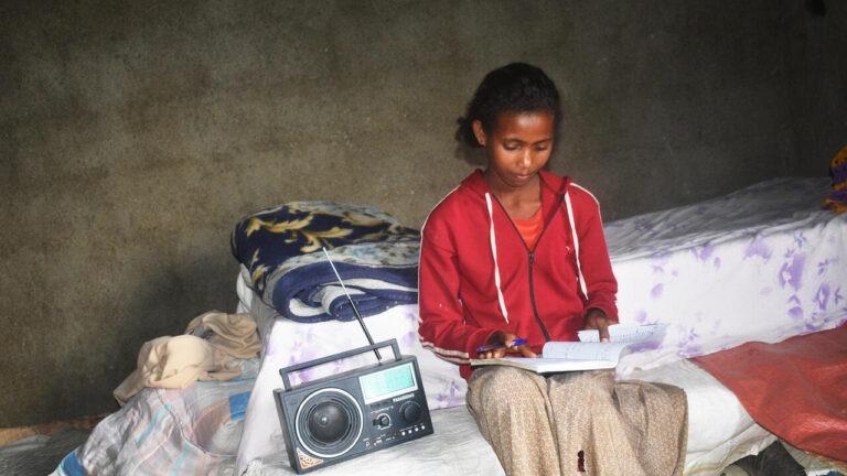 Etiopialaistyttö istuu penkillä ja kuuntelee kouluopetusta radiosta
