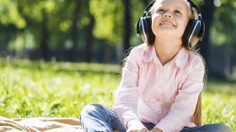 tyttö istuu nurmikolla kuulokkeet päässä