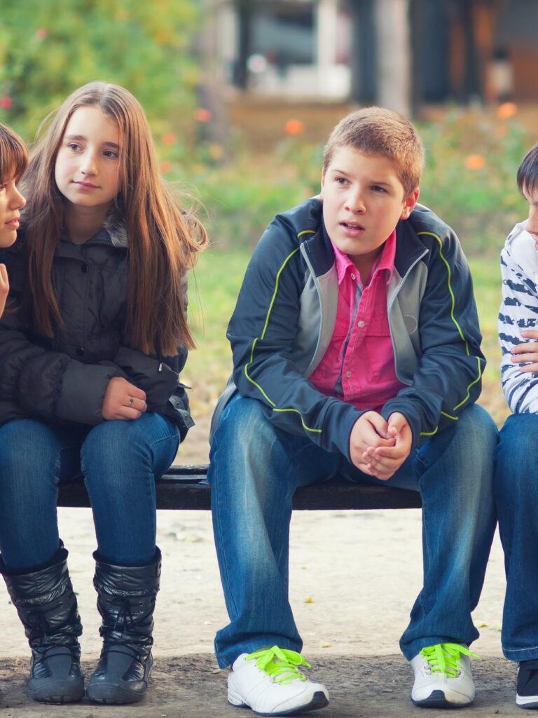 teini-ikäiset rivissä penkillä