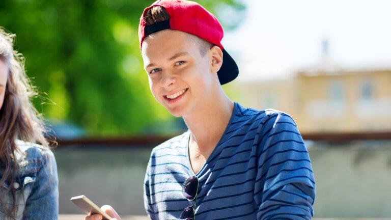 Nuori poika kännykkä kädessä