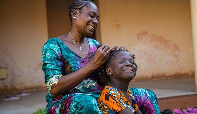 Afrikkalaisäiti letittää lapsensa hiuksia kotitalon portailla.