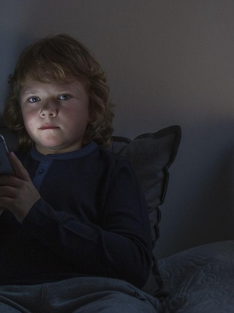 lapsi pimeässä huoneessa puhelimen valossa