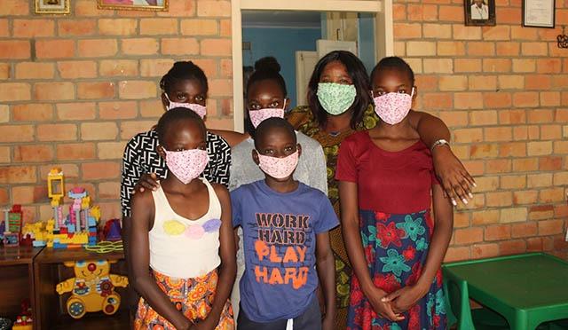 Sambialainen lapsikylä-äiti lasten kanssa ryhmäkuvassa.