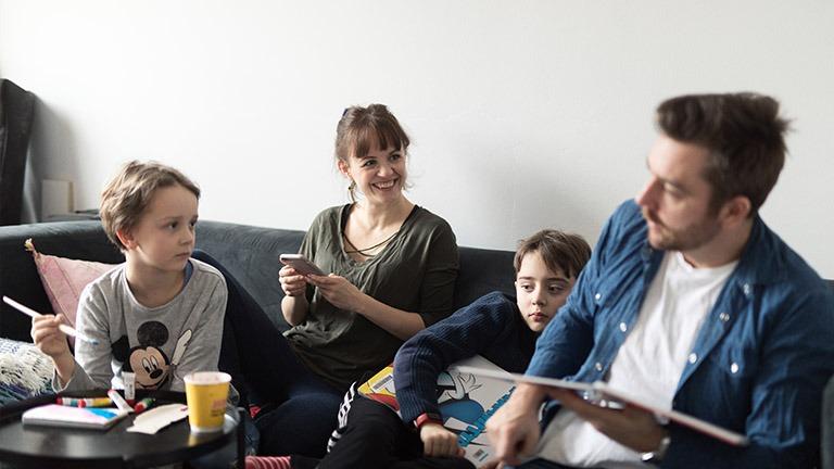 Perhe istuu sohvalla