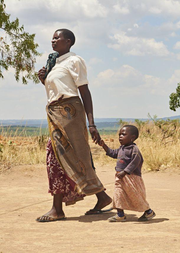 Tansanialaisnainen taluttaa pientä lastaan