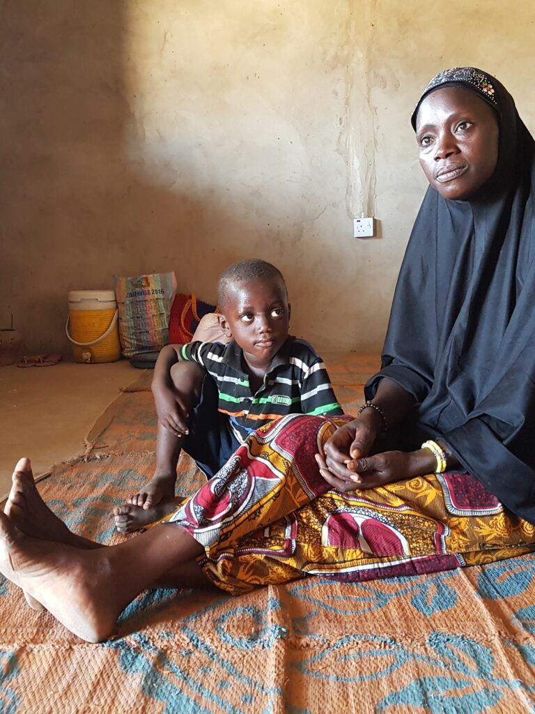 Äiti ja lapsi istuu maassa kodissaan Gambiassa