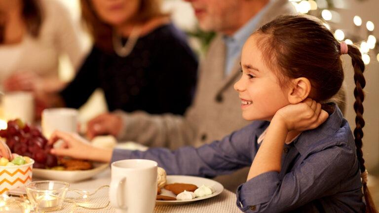 Tyttö istuu illallispöydässä