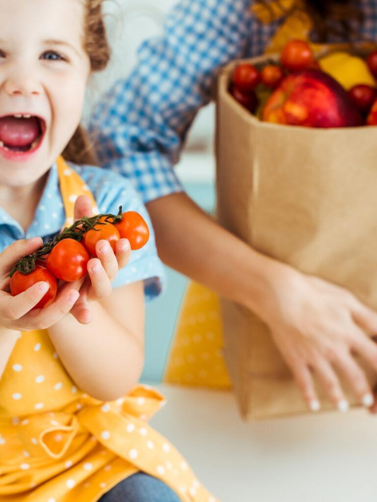 Lapsella innosutnut ilme, pitelee kirsikkatomaatteja kädessä