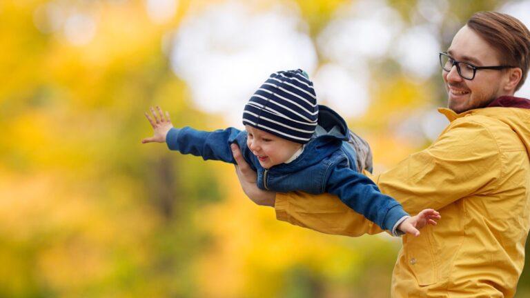 Isä ja lapsi leikkivät puistossa syksyllä.