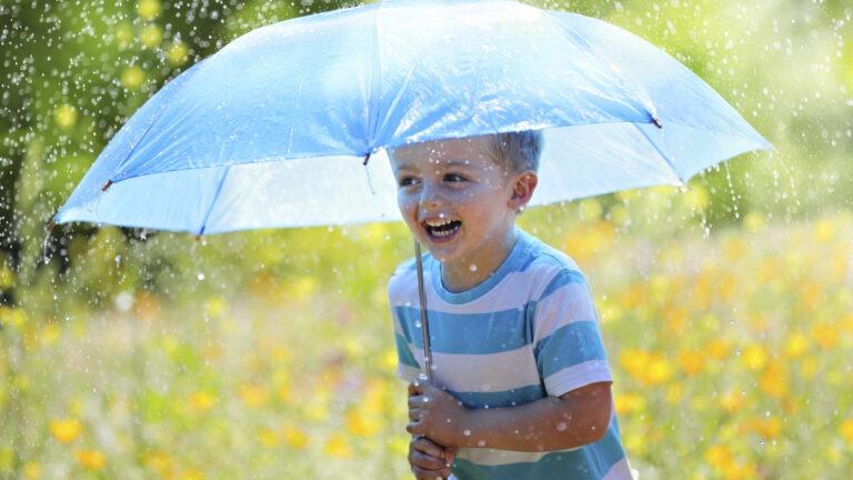 Poika sateessa sateenvarjon alla