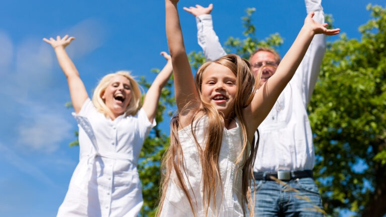 Perhe hyppää iloisena ilmaan