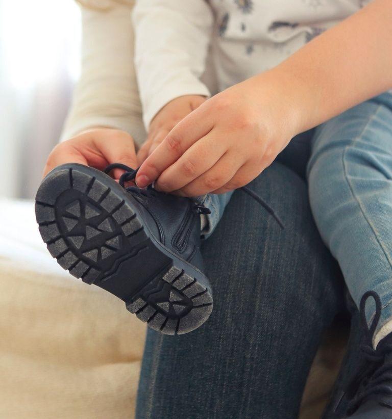 Aikuinen auttaa lasta solmimaan kengännauhat