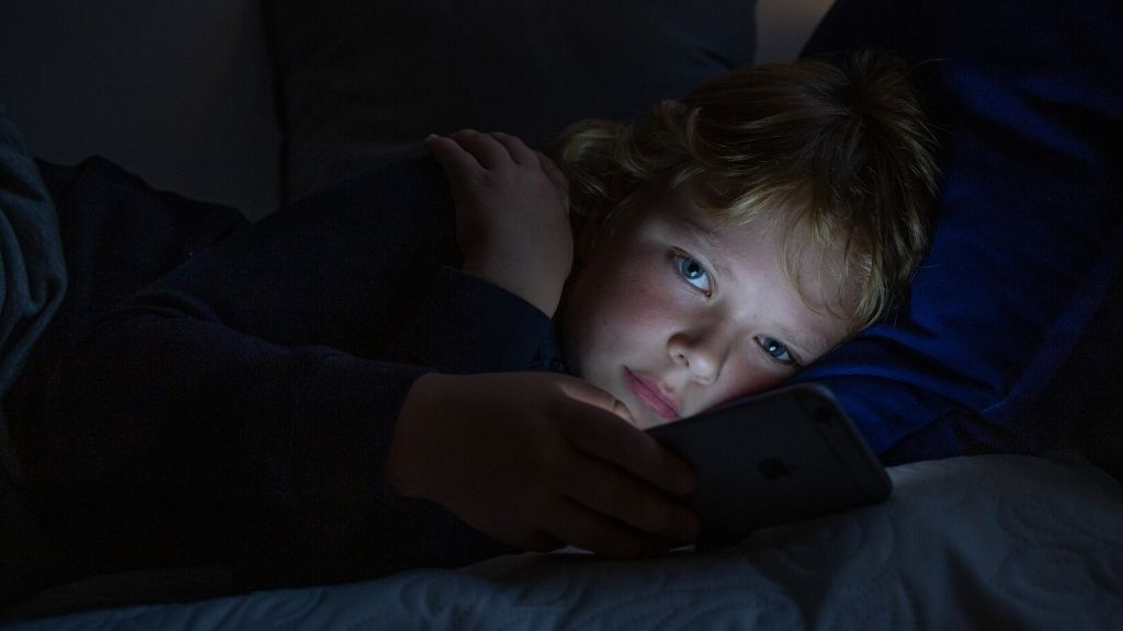 Apuu-chattiin yhteyttä ottava lapsi pimeässä huoneessa