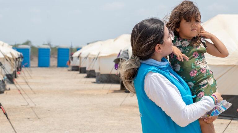 SOS-lapsikyläjärjestön työntekijä pitää sylissä tyttöä Columbian hätäapuleirillä