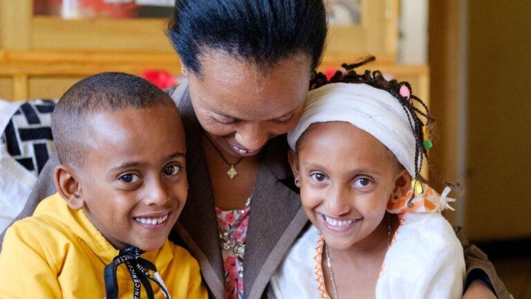 Etiopialaiset kaksoset lapsikylä-äitinsä kanssa hymyilevinä