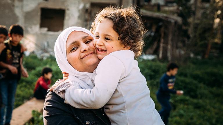 äiti syleilee lasta Syyriassa