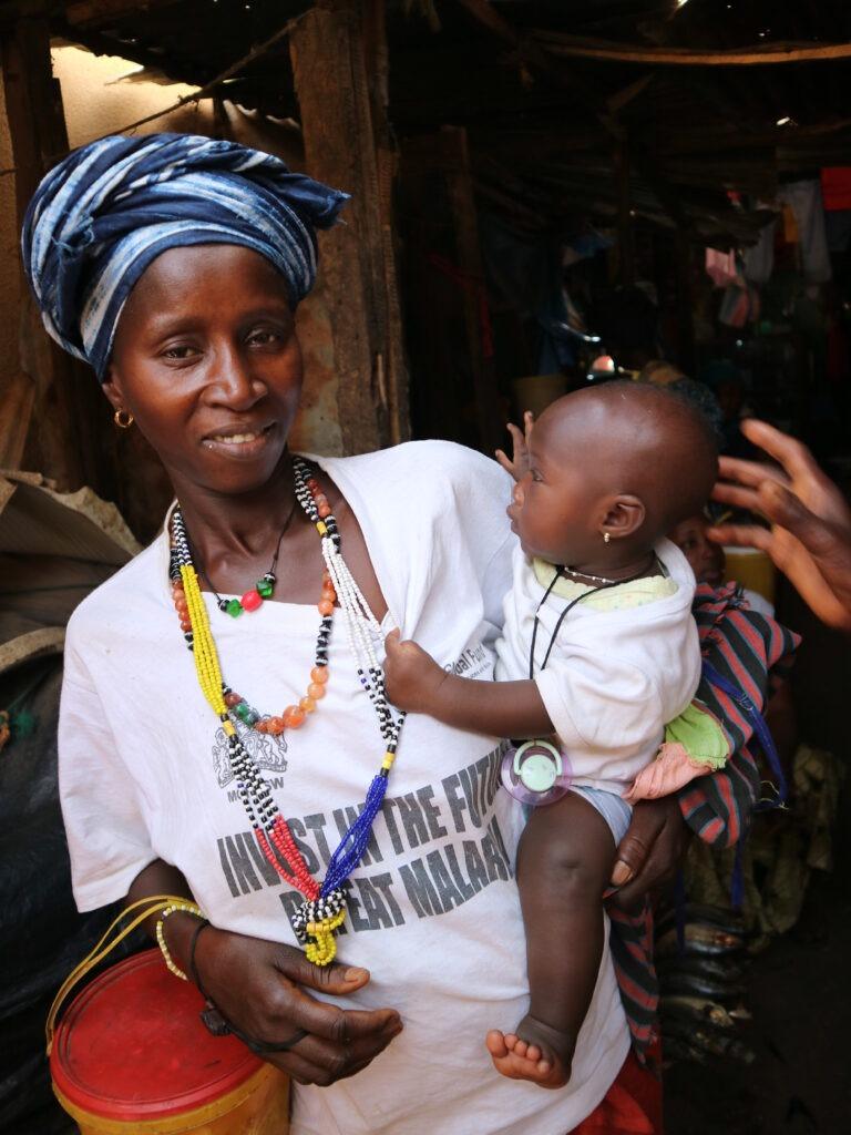 Äiti pitelee tytärtä sylissä Gambiassa