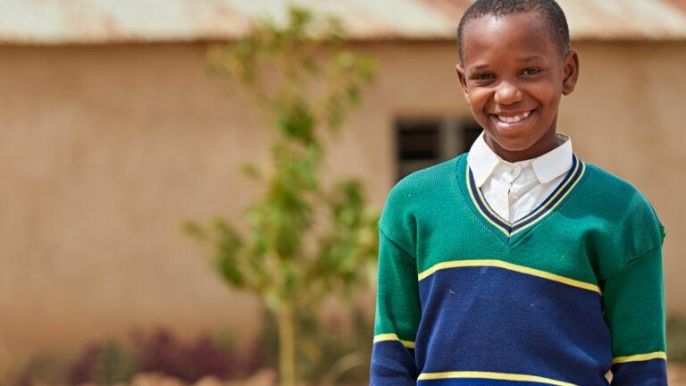 Lapsi koulupuvussa koulun edessä Tansaniassa
