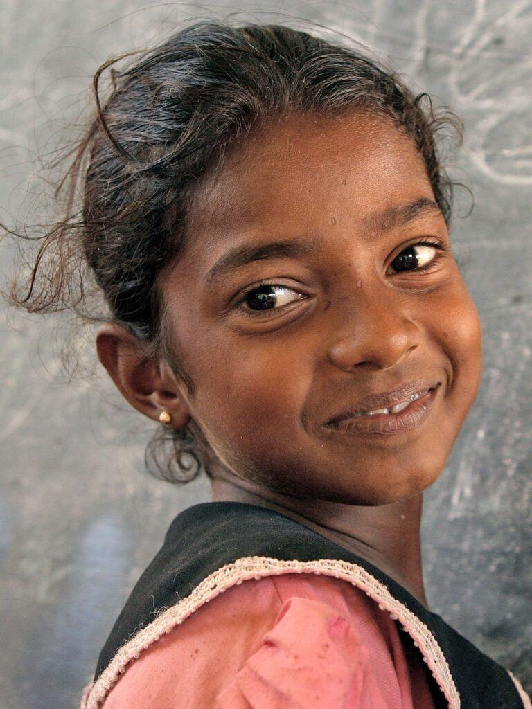 Tyttö hymyilee liitutaulun edessä Komarin aluella, Sri Lankassa.