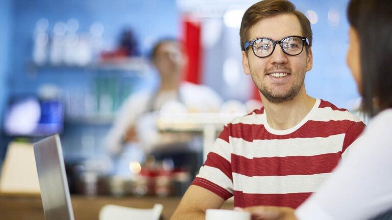 mies kahvilassa nuoren kanssa