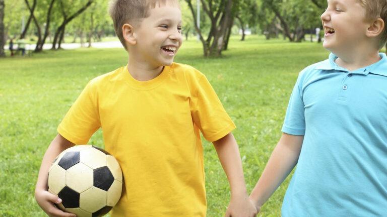 pojat käsikädessä jalkapallo mukana