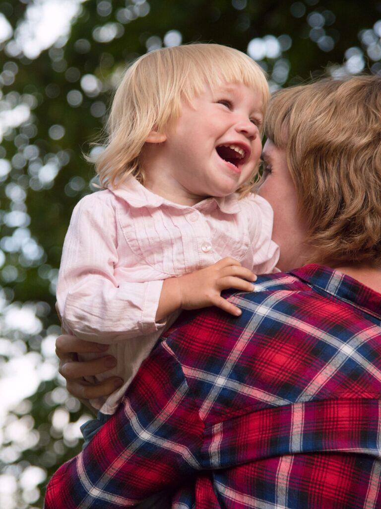 ruutupaitainen äiti pitää auravaa lasta sylissä