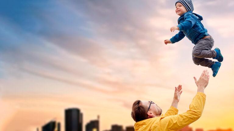 Isä leikkii lapsen kanssa heittämällä tätä ilmaan.