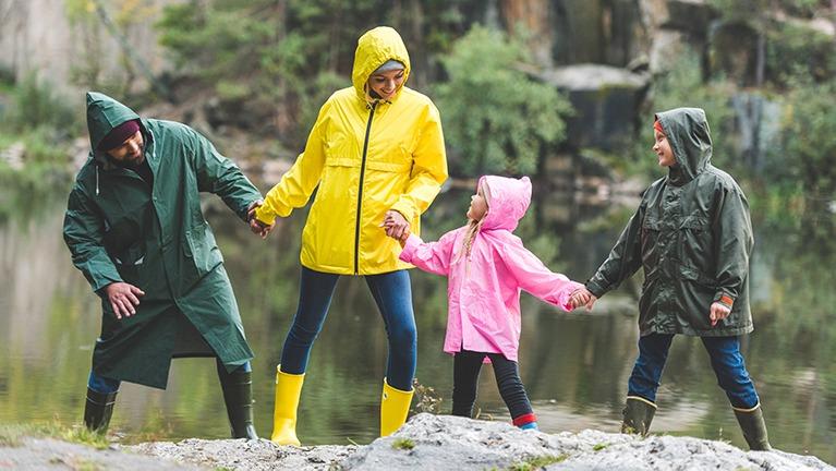 Sadetakkeihin pukeutunut perhe pitää toisiaan kädestä kiinni kalliolla.