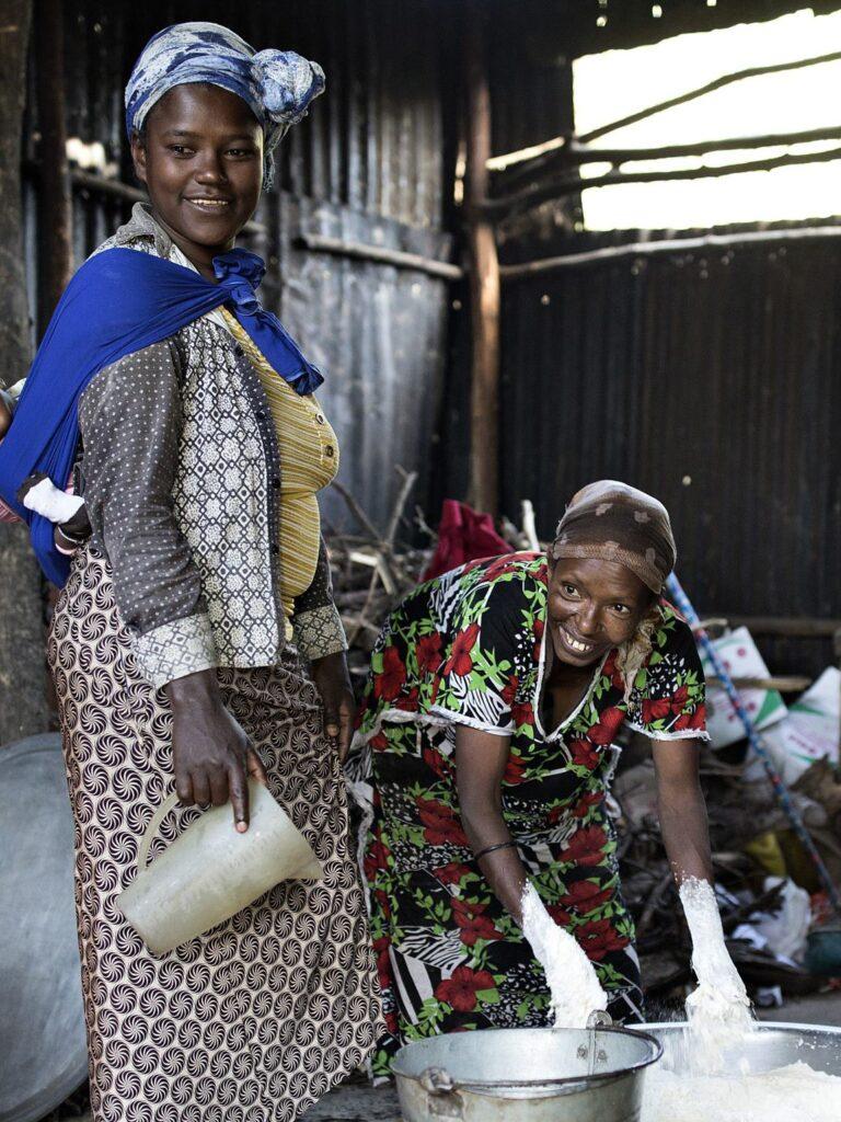 Etiopialaisnainen ruuanlaitossa lastensa ja äitinsä kanssa