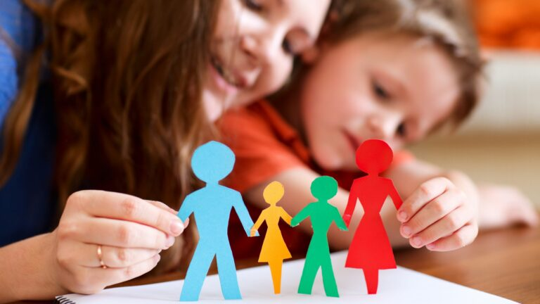 Äiti ja lapsi pitävät käsissään moniväristä paperista leikattua perhettä.