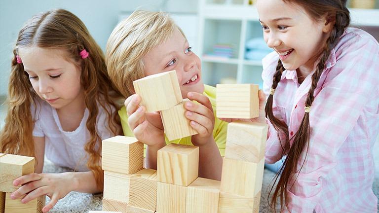 Kolme tyttöä leikkii palkikoilla